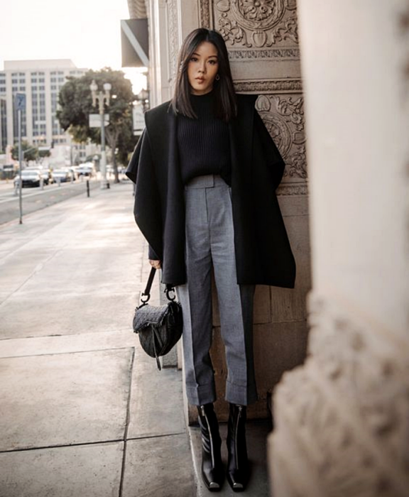 girl with long brown hair wearing a black sweater, black oversized big coat, gray dress pants, black high heel ankle boots and black handbag