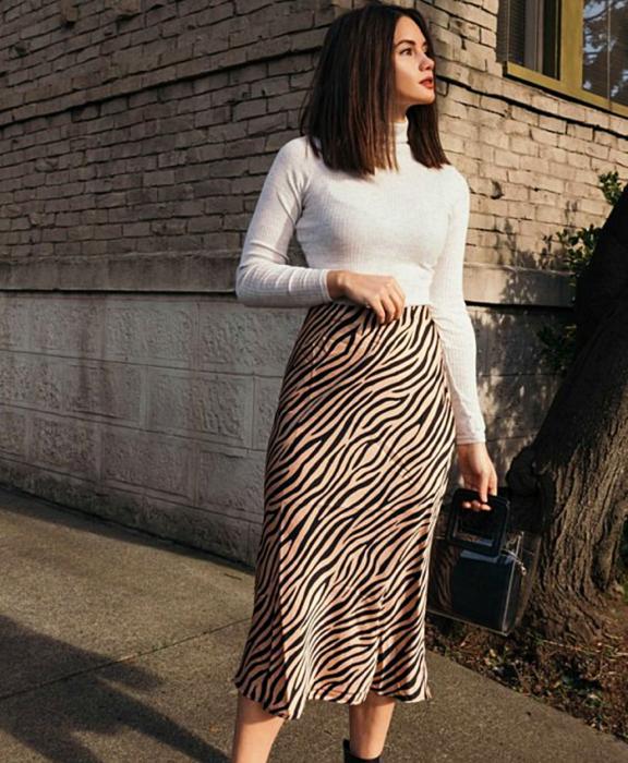 chica de cabello castaño usando un top de manga larga blanca con cuello alto, falda larga de satén con estampado de cebra y bolso negro de mano