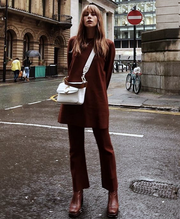 blonde girl wearing a brown turtleneck top, brown coat, brown dress pants, brown ankle boots and white leather handbag