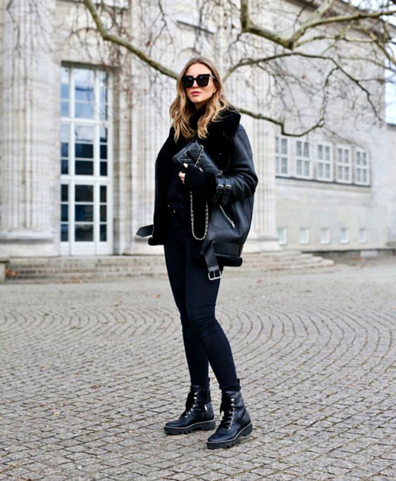 blonde girl wearing sunglasses, a black top, black leather coat with fur, black skinny jeans, black thick-soled ankle boots and black bag with gold chain