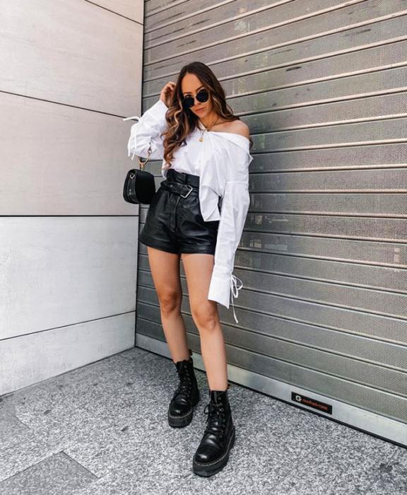 chica de cabello castaño largo usando lentes de sol, camisa blanca a los hombros, bolso pequeño negro, shorts cortos de cuero, botas de plataforma negras