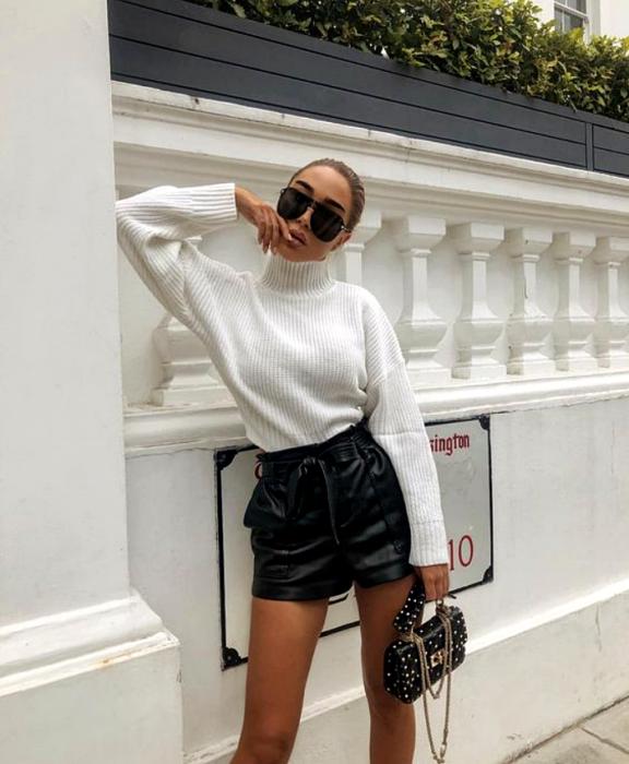 chica rubia usando lentes de sol, suéter blanco de cuello alto, shorts cortos de cuero negro y bolso de mano pequeño