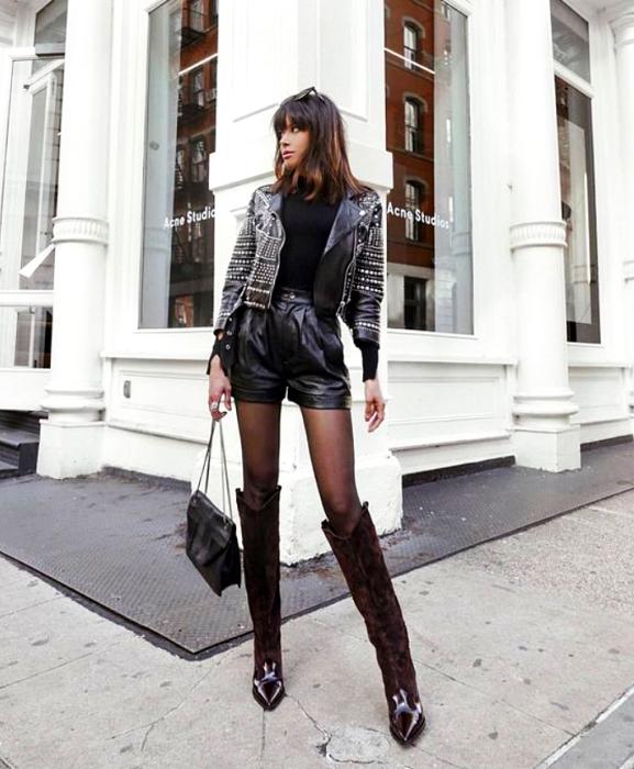 chica de cabello castaño usando un top negro, blazer saco de cuero con estoperoles, shorts cortos de cuero, botas largas cafés y bolso pequeño de mano