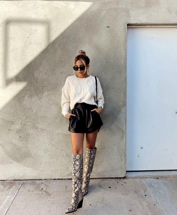 chica rubia con lentes de sol usando suéter blanco, shorts cortos de cuero, botas largas de estampado de serpiente y bolso negro pequeño