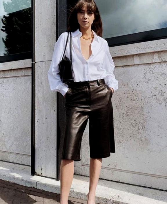 chica de cabello castaño largo usando una camisa de botones blanca con collar dorado, bolso pequeño negro de cuero, shorts tipo bermudas negras de cuero