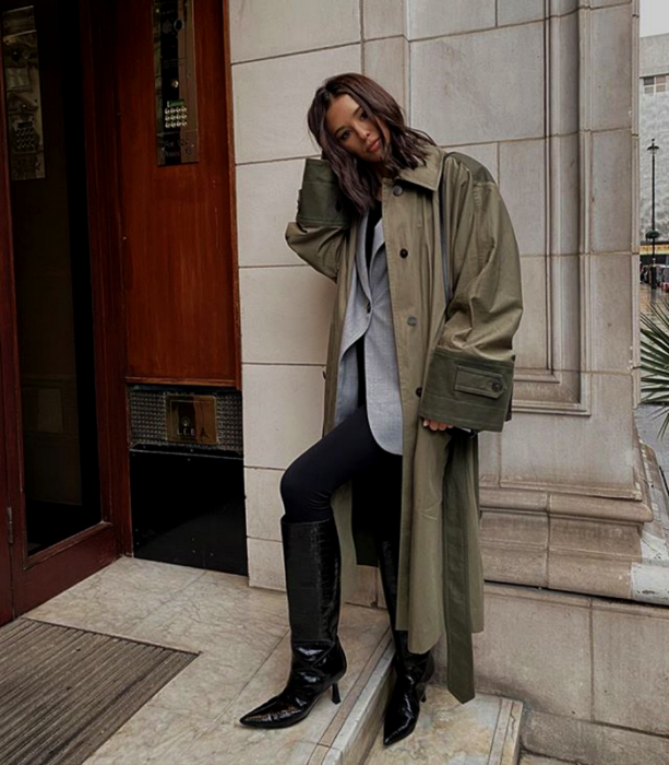 long brown hair girl wearing long army green coat, gray jacket, black leggings, long black heeled boots