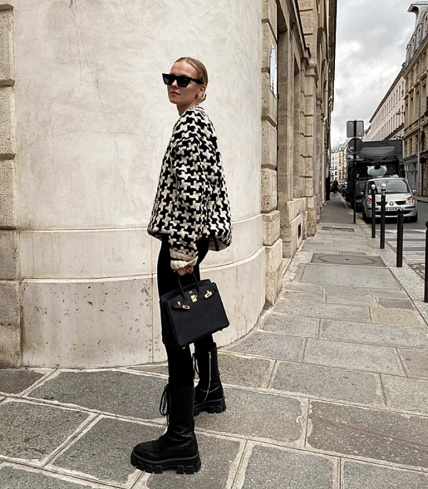blonde girl with sunglasses wearing white and black plaid sweatshirt, black leggings, black leather boots and black leather mini bag