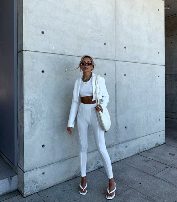 blonde girl wearing a white crop top, white blazer, white leggings, white mini bag and white flat sandals