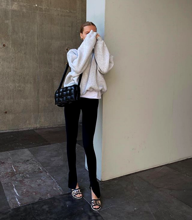 blonde girl wearing a white sweatshirt, white top, black clutch bag, black leggings and white high heel sandals