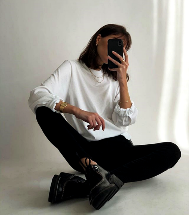 brown haired girl wearing a white sweatshirt, black leggings and black platform shoes