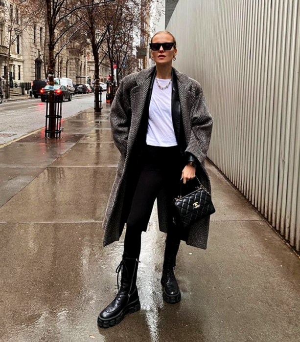 blonde girl wearing sunglasses, white top, leather jacket, long plaid coat, black leggings and black platform ankle boots and black handbag