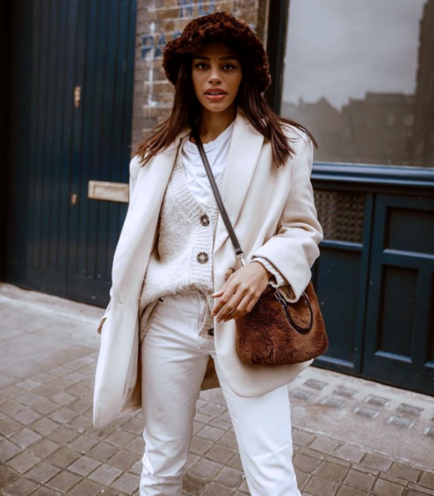 brunette girl wearing an animal print fur bucket hat, beige coat, white sweater and white pants
