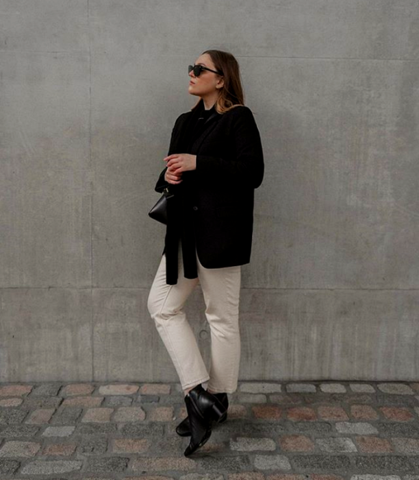 blonde girl wearing sunglasses, black coat, white pants and black leather ankle boots