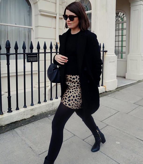 chica de cabello corto oscuro usando lentes de sol, top negro, abrigo negro, falda de animal print, medias negras y botines negros y bolso de mano negro