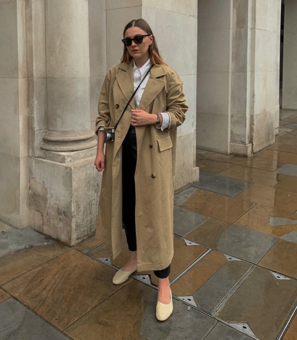 blonde girl wearing a light brown coat with sunglasses, black pants, white turtleneck and beige ballerinas