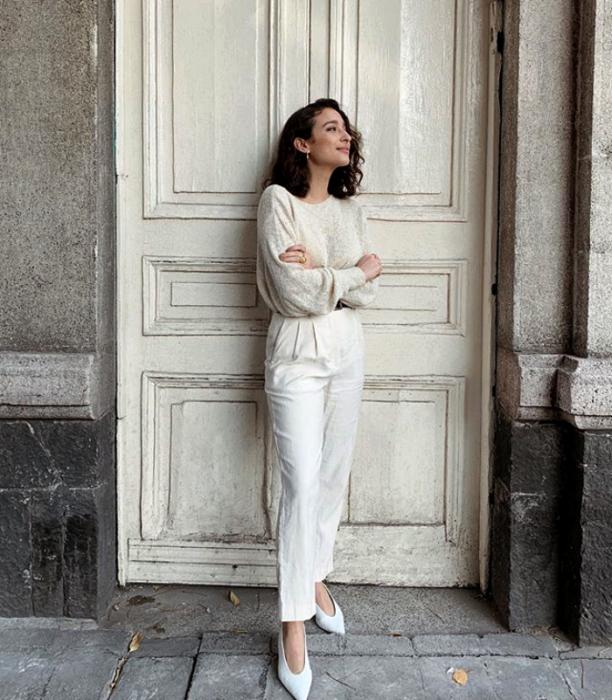 chica de cabello corto con pantalon blanco, suéter blanco y zapatillas blancas