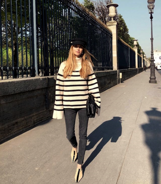 blonde haired girl wearing black and white striped sweater, leggings and floor sneakers with black beret