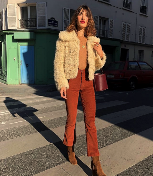 Long brown haired girl wearing a white shag coat with an orange top and red pants and ankle boots