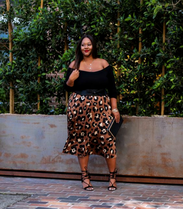 Long dark hair brunette curvy girl wearing a 3/4 black off shoulder top with animal print midi skirt, black high heeled sandals and black handbag