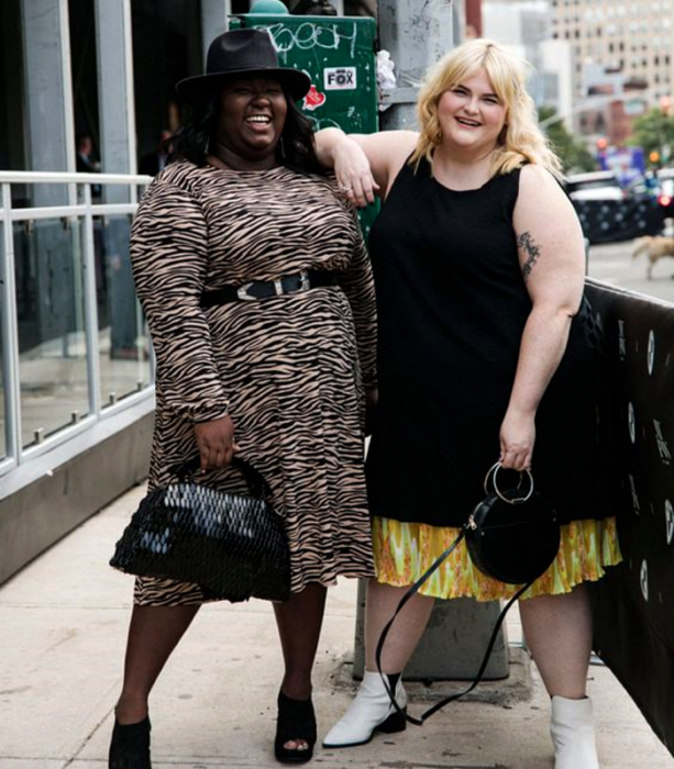 curvy girls, a blonde in a long sleeveless black dress and yellow skirt with orange underneath, white ankle boots and a black bag, another brunette girl in a black hat, long-sleeved animal print dress, black handbag and black high-heeled sandals