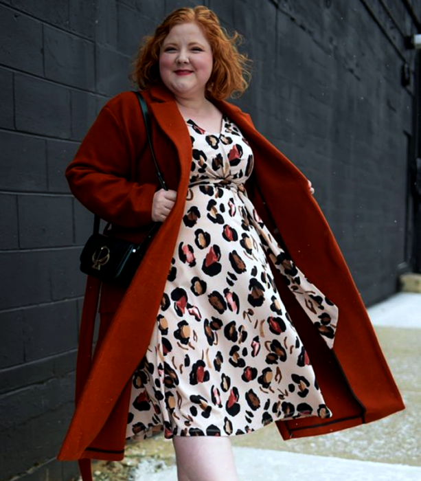 curvy redhead girl wearing long orange coat, black fur bag and animal print midi dress