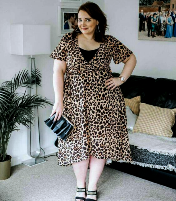 curvy brown haired girl wearing short sleeve v neck animal print midi dress, black clutch bag and black heeled sandals