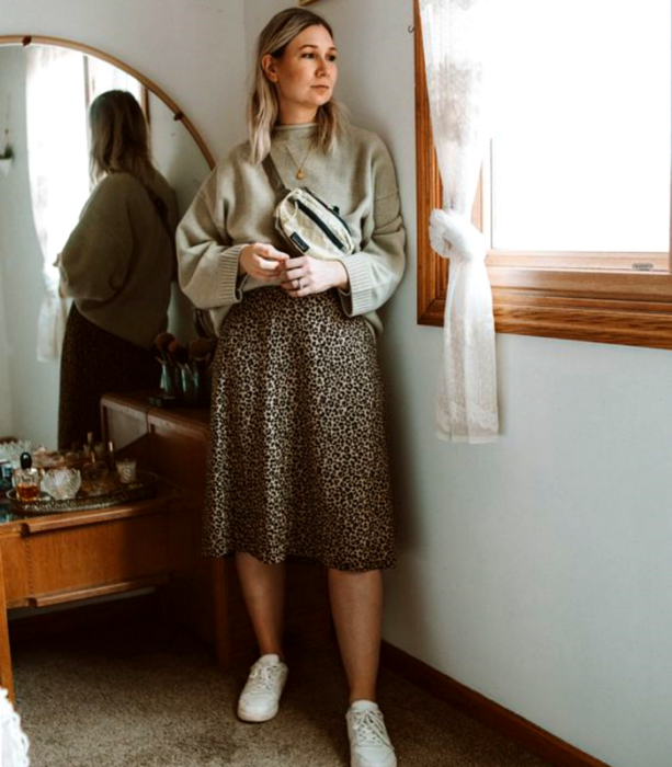 Curvy blonde girl wearing beige sweater, animal print midi skirt and white low top sneakers