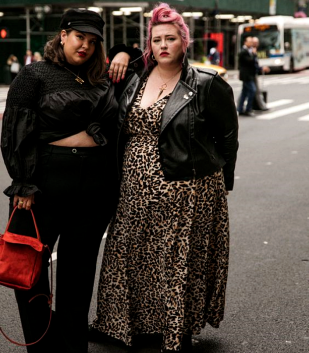 curvy girls, one wearing a black beret, black long-sleeved blouse, black high waist jeans and red handbag, another with pink hair, leather jacket, long animal print dress