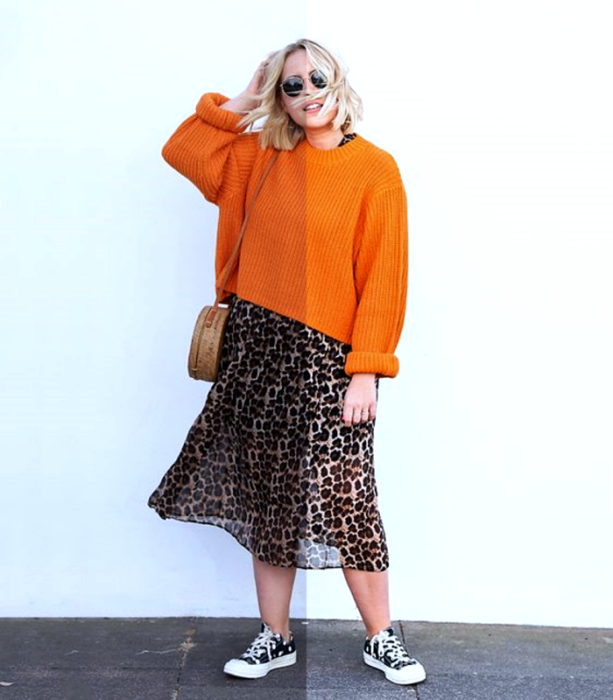 blonde girl wearing sunglasses, orange sweater, animal print midi skirt and black converse sneakers, beige handbag