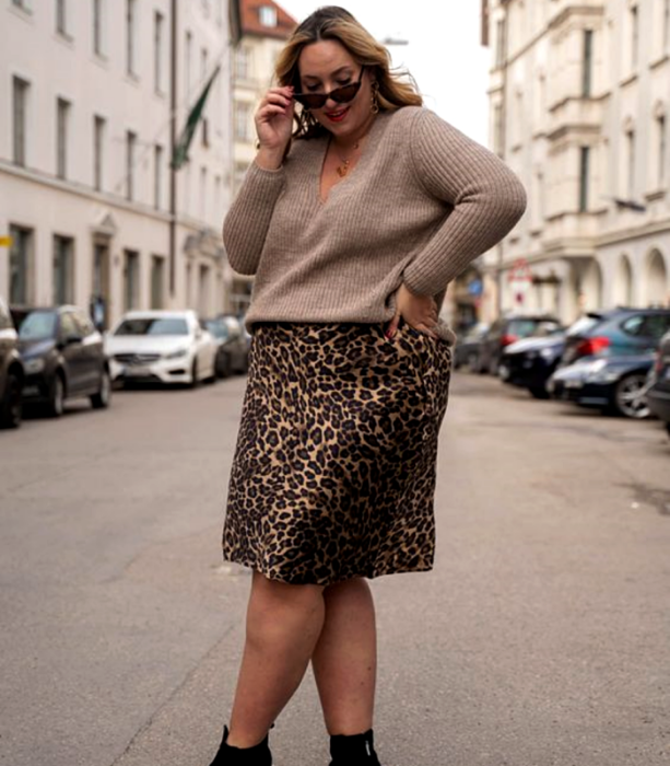 curvy girl wearing sunglasses, brown sweater and animal print midi skirt with black booties