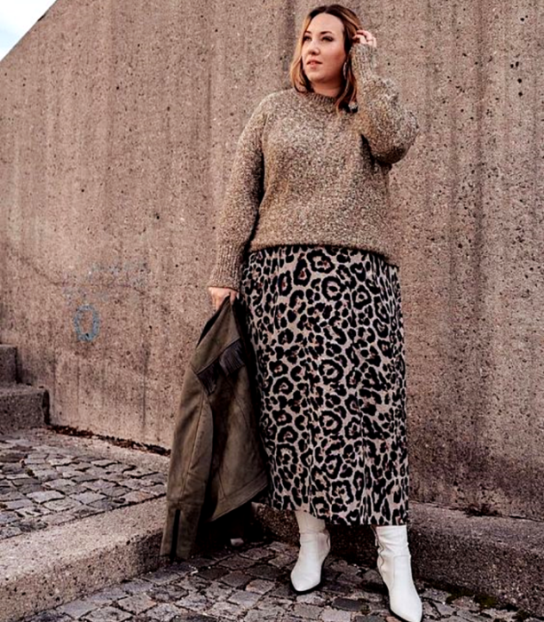 Blonde curvy girl wearing brown sweater with long animal print skirt, brown coat and white booties