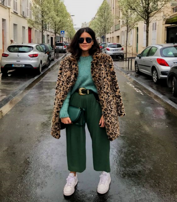 curvy brown haired girl wearing blue sweater with animal print coat, green culottes, white tennis shoes and green tote bag