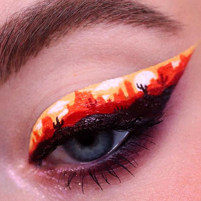 maquillaje de ojos con delineado negro con naranja y blanco, recreando un paisaje