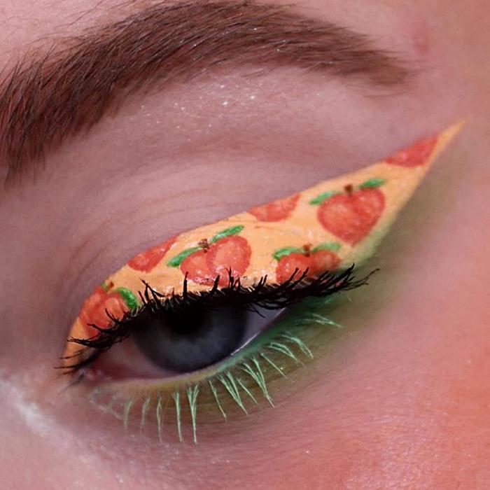 maquillaje de ojos con delineado color naranja claro con dibujos de emoji de durazno y delineado verde y rímel negro y verde