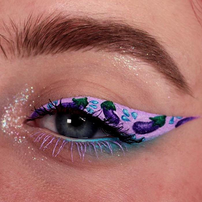 maquillaje de ojos morado con emojis de berenjena y delineado rosa