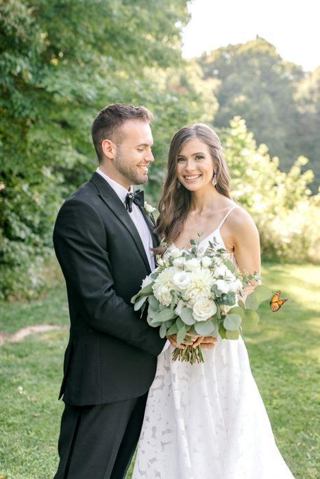 Pareja de novios posando para una sesión de fotos el día de su boda junto a una mariposa en un gran jardín