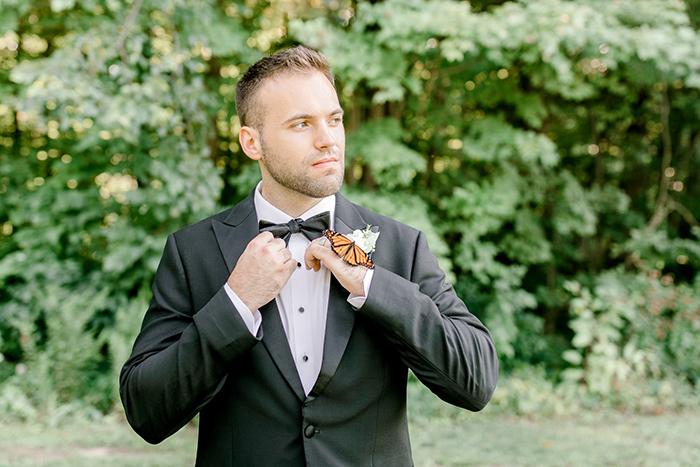 Novio posando para su sesión de fotos de boda mientras una mariposa se posa en su mano