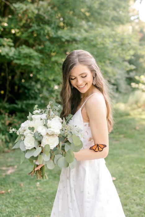 Novia sujetando su ramo mientras posa para una fotografía y una mariposa aparece cerca