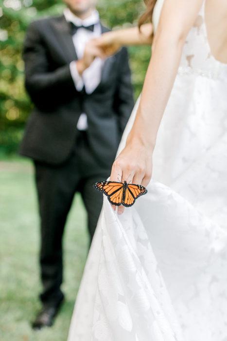 Pareja de novios posando junto a una mariposa en un hermoso jardín