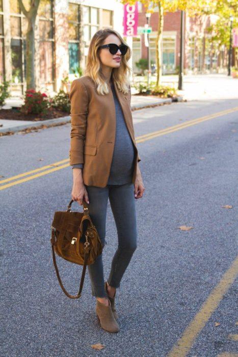 Chica usando un outfit de maternidad de jeans, saco color café y botines