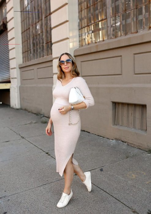 Chica usando un outfit de maternidad de vestido de color beige con tenis