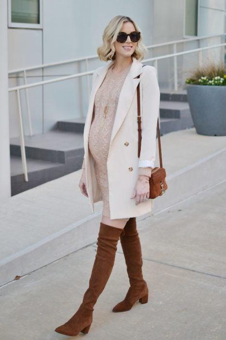 Chica usando un outfit de maternidad de vestido con saco largo y botas hasta los muslos
