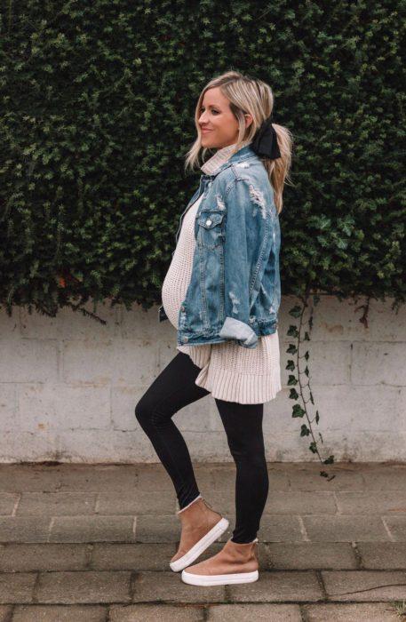 Chica usando un outfit de maternidad de leggins, bluson, tenis y chaqueta de mezclilla