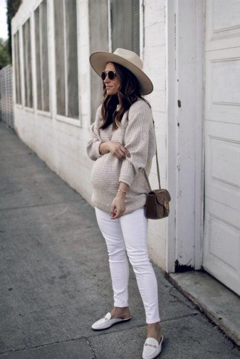 Chica usando un outfit de maternidad de jeans blancos, sueter color café y sombrero