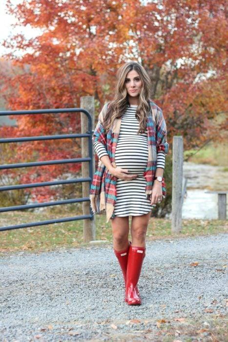 Chica usando un outfit de maternidad de vestido con rayas, botas de lluvia y poncho