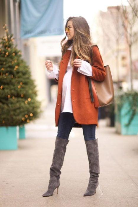 Chica usando un outfit de maternidad de jeans con botas altas, blusa blanca y saco color ladrillo