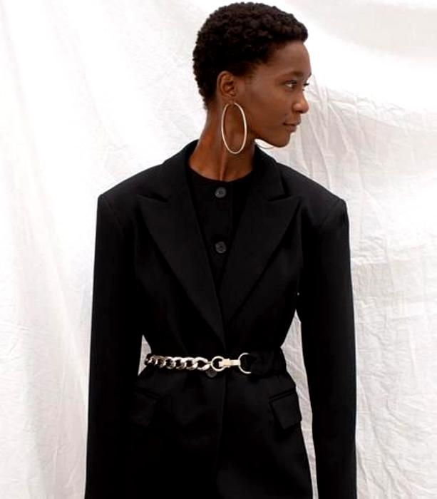 chica morena con traje negro de vestir formal con cinturón metálico plateado