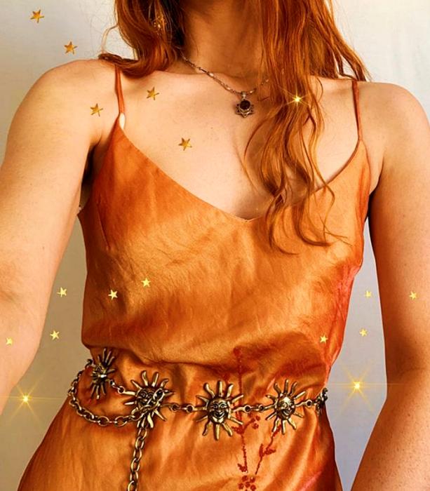 chica pelirroja usando un vestido de satén naranja con cinturón metálico dorado de soles