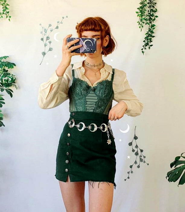red-haired girl wearing beige long-sleeved shirt, green strappy corset, green corduroy skirt with metallic moons belt