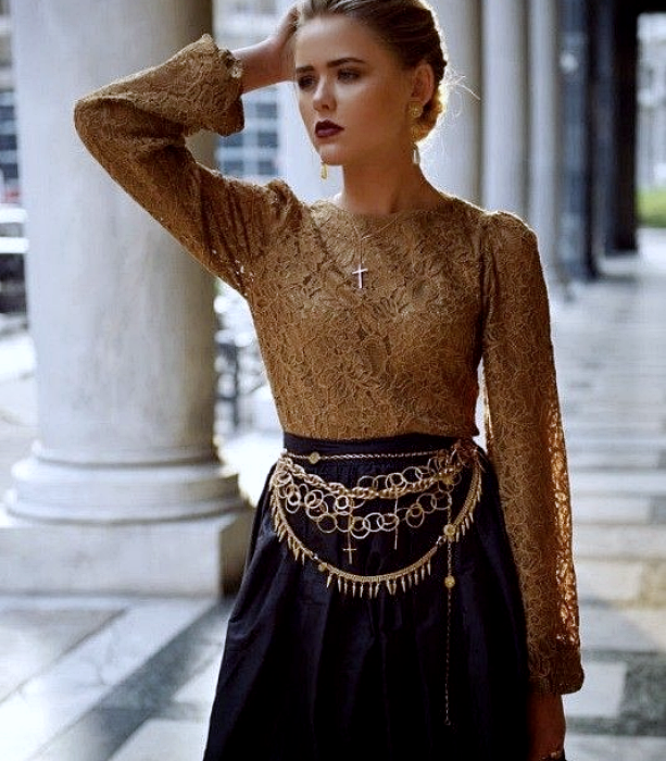 light haired girl wearing yellow blouse with baggy sleeves, black skirt with gold metallic belt